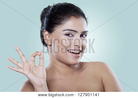 Portrait of young indan woman with healthy and clean skin showing OK hands in the studio