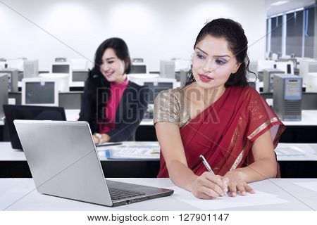 Portrait of Indian businesswoman wearing sari clothes and working in the office with her partner