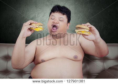 Photo of a young obese man sitting on the sofa while eating two cheeseburgers