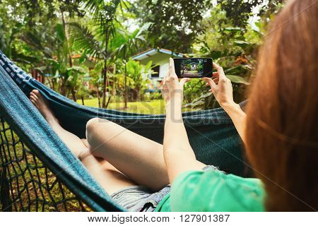 girl lying and taking a photo in a hammock in the tropical jungles of Brazil. Brasil