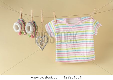 baby goods hanging on the clothesline. Beige background