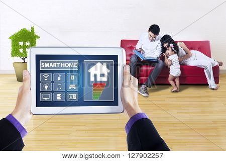 Hands holding a tablet computer with smart house technology system on the screen shot with happy family on the sofa