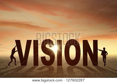 Silhouette of two businesswomen with a vision word at field shot at sunset time