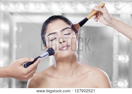 Lovely young model closing her eyes while two hands of makeup artist apply makeup on her cheek