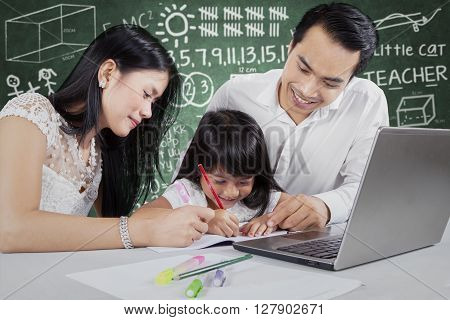 Portrait of two young parents helping their daughter doing homework with a laptop on the table