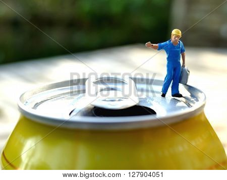 Miniature Workman Carrying Heavy Jerrycan On Top Of Soda Can With Blurred Background. Business Conce