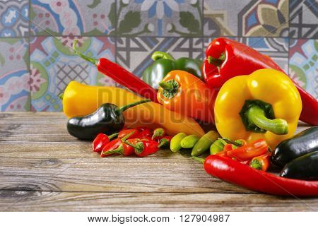 Mexican hot chili peppers colorful mix paprika poblano serrano jalapeno on ornamental and wooden background