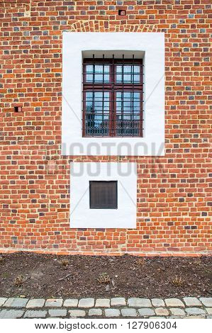 Two old square windows one with steel grating. Old red brick wall.