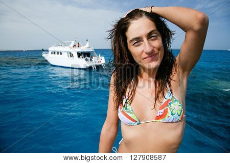 brunette woman in bikini hand in hair looking behind a boat or yacht ready to diving in blue ocean water in Red Sea next to Sharm al Sheij and Hurghada Egypt Africa