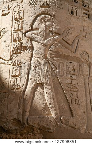 Egyptian carving figure and hieroglyphs in column of landmark Temple of Ramses or Ramesses III at Medinet Habu monument in Luxor Egypt Africa