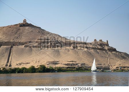 landscape from water Nile River of landmark archeological mountain with nobles tombs in Qubat El ?Hawa tower and Egyptian boat with white sail in Aswan Egypt Africa