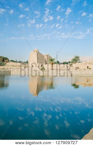 landscape of Sacred Lake and ancient building with palms in landmark Egyptian Karnak Temple public monument declared a World Heritage by Unesco in Luxor Egypt Africa