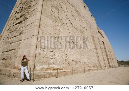tourist woman in corner of wall facade of landmark Egyptian Temple of Ramses or Ramesses III at Medinet Habu monument with carving figures and hieroglyphs in Luxor Egypt Africa