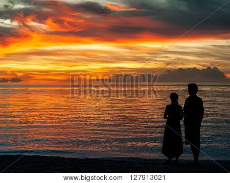 A couple staring at the sunset on the sea
