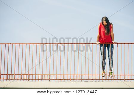 Young long haired girl raise up on railing above the urban bridge. Lifestyle funky in summer. Trendy sport teen looking down.