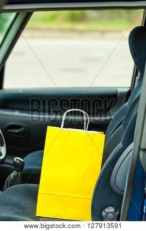 Bag on driver seat. Yellow shopping handbag inside car.