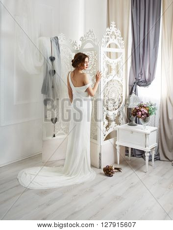Wedding dress with train fashion. Beautiful young bride in vintage wedding dress indoors. White wedding dress at model. Wedding fashion in decorated shabby chic interior with flowers, high key.