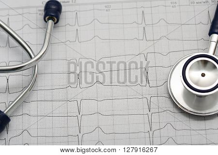 Stethoscope Head Lying On Cardiogram On Clipboard Pad