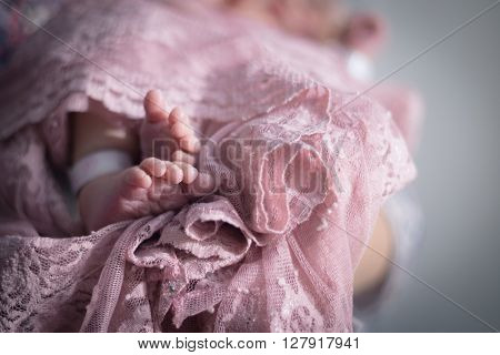 Baby's feet wrapped in pink lace swaddle