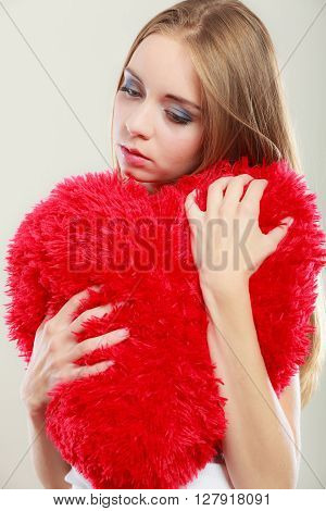 Broken heart love concept. Sad unhappy woman hugging red heart pillow closeup