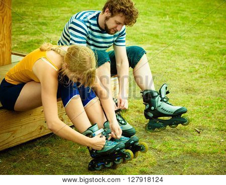 Woman And Man Putting On Roller Skates