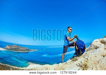 male traveler with backpack  standing on the trail against sea and blue sky at early morning. Balos beach on background, Crete, Greece