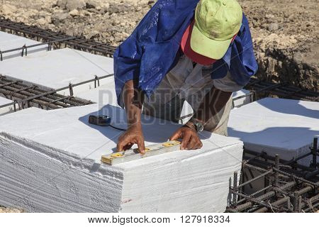 Worker levelling an Iron framework and polyurethane  to build a foundation for a building