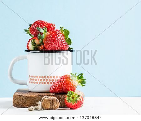 Fresh ripe red strawberries in country style enamel mug on rustic wooden board, pastel light blue background, selective focus, copy space