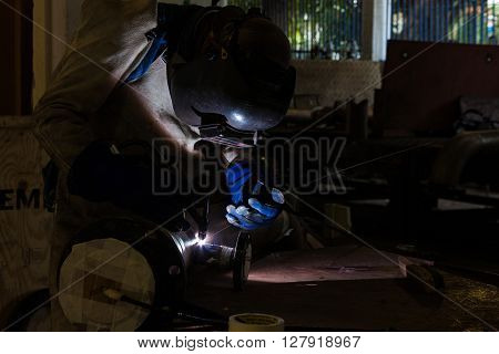 Man welding in the dark wearing protective clothes and equipment