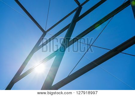 Steel construction with sky background and shining sun. Sun beams. Modern business building construction. Sun burst on blue sky with steel construction.