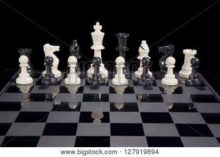 A chess board with black and white pieces together as a team