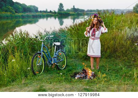 Woman in Folk costume with bicycle. Young attractive woman at the riverside having rest with bicycle in national ethnic ukrainian folk traditional costume or dress. Girl standing near bonfire.