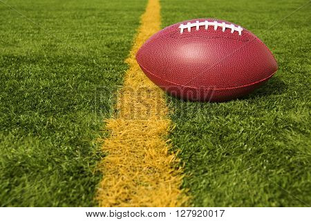 An American football resting just over the goal line for a touchdown