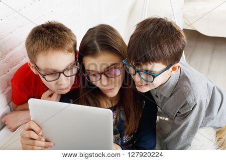 Group of kids in eye glasses look into tablet. Children computer games, social networks and media addiction concept. Girl and boys with tablet. Communication technologies. Eyesight, eyewear for kids.