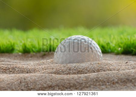 Golf ball in sand bunker nature background