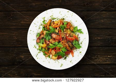 Restaurant food - roasted potatoes with vegetables and mushrooms, parsley at dark brown rustic wood background. Top view.