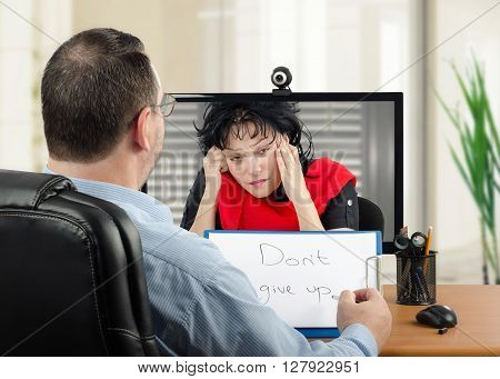 Online psychiatrist uses video conferencing to communicate remotely with depressed woman with red scarf in monitor. Middle-aged psychotherapist stares and listens her. He has just written message Dont give up and ready to show it to her.