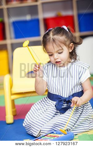 Little girl singing and playing a xylophone