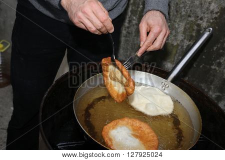 Cooking The Big Fried Fritters Dipped In Boiling Oil In An Alumi