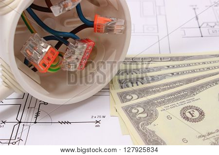 Copper wire connections in electrical box and money on construction drawing of house concept for engineering and energy savings