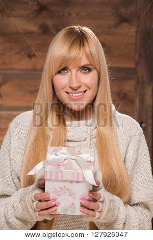 Smiling woman in pullover with christmas gift
