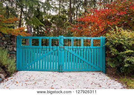 Blue gates against autumn trees on the background. Rural landscape entrance gate