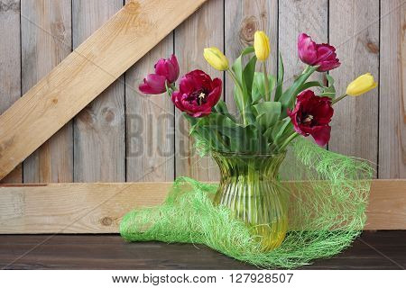 Spring bouquet Burgundy and yellow tulips on the background of boards. Still life with tulips.