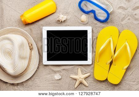 Tablet computer with blank screen on beach sand with beach items top view. Summer background