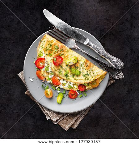 Healthy breakfast. Omelette with vegetables. Black background