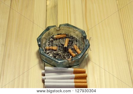 Shot of an ashtray with some finished cigarettes in it next to some untouched ones ** Note: Shallow depth of field
