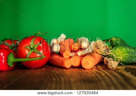 Vegetables on a wooden table with green screen in behind