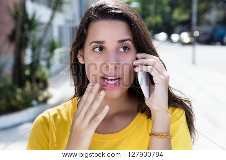 Shocked caucasian woman in yellow shirt listening at phone outdoor in the city with street and buildings in the background