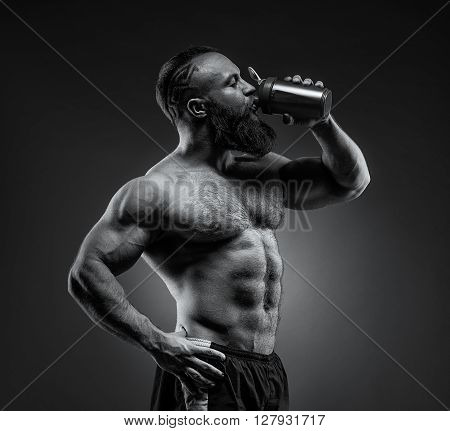 Bearded Man Bodybuilder Posing On Gray Background