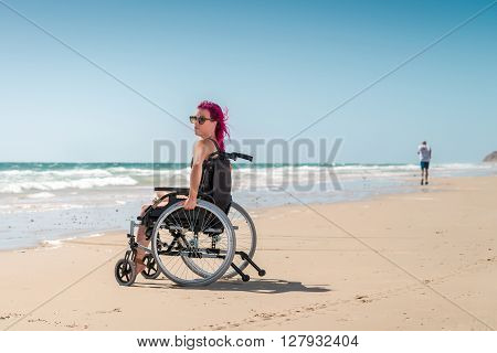 Disabled woman enjoys the beach and sun while the man was running by